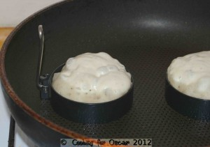 Pouring the crumpet batter into the egg rings